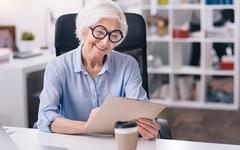 Amused aged woman working in the office Stock Photos