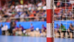 Handball match scene with goalpost and players in the background Stock Footage
