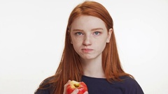 Concentrated red-haired teenage Caucasian girl eating apple chewing fast on Stock Footage