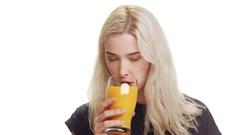 Young cute smiling blonde girl wearing dark blue shirt drinking orange juice Stock Footage