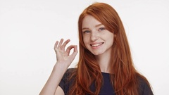 Smiling cute redhead Caucasian teenage girl showing ok on white background in Stock Footage