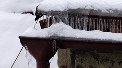 The look at snow and ice at the eaves and on the roof of the house Stock Footage