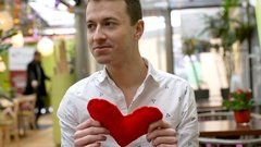 Handsome man holding handmade heart and smiling to the camera, steadycam shot Stock Footage