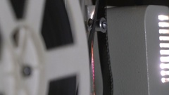 Vintage 8 mm movie projector close up. Visible perforation on the film passes Stock Footage