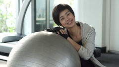 Beautiful fit Asian girl with pilates ball in gym Stock Footage
