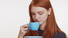 Beautiful Caucasian foxy teenage girl drinking from blue cup and saucer smiling Stock Footage