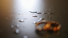 Golden wedding rings on table with drops of water, rack focus Stock Footage