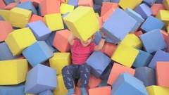 Happy Little Kid Girl Playing at Colorful Soft Foam Cubes Playground High V.. Stock Footage