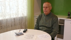 Old man with receipt for communal services at the table on the kitchen Stock Footage