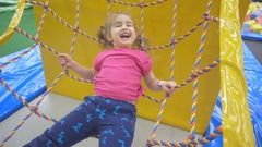 Girl swinging on the Hammock Ropes Course with Long Fair Hair in Indoors Pl.. Stock Footage