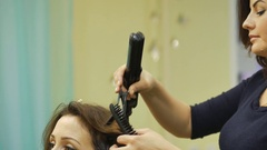 Hairdresser using straightener on beautiful woman hair in hair salon. Curling Stock Footage