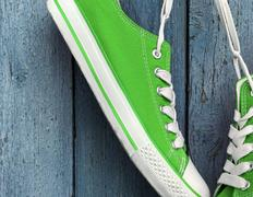 Bright green textile sneakers hanging on the white lace Stock Photos