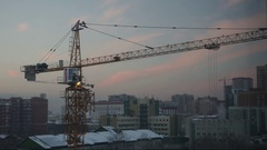 A large construction crane is collected in all rows at dusk, time lapse Stock Footage
