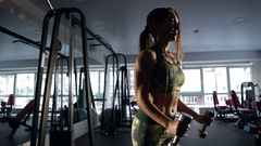 Sporty girl showing her well trained body and lifting dumbbells . Stock Footage