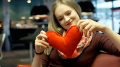 Girl holds red, handmade heart and thinks abut something in the cafe Stock Footage