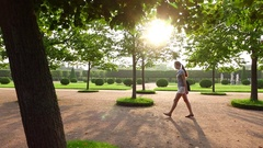 Track shot, young woman walk at gorgeous formal garden, sun flash through leaves Stock Footage