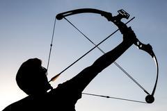 Archer draws his compound bow silhouette Stock Photos