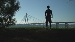 A silhuette video of a young man warming up for the training outside Stock Footage
