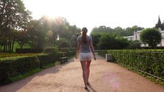 Girl stoll along empty path in beautiful formal garden, POV camera follow behind Stock Footage