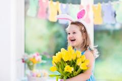 Little girl in bunny ears on Easter egg hunt Stock Photos