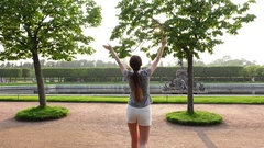 Happy girl come at beautiful park, rise hands and touch clipped trees leaves Stock Footage