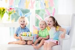 Kids with bunny ears on Easter egg hunt Stock Photos