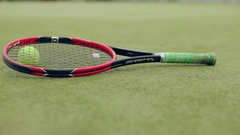 Tennis balls and racket on the grass court Stock Footage