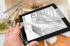Hand on Computer Tablet Showing Drawing of Kitchen Photo Behind with Compas.. Stock Photos