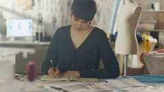 Beautiful Female Fashion Designer Artist Sitting at Her Desk Drawing Sketches  Stock Footage