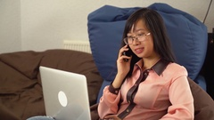 Girl with laptop and cellular telephone indoors Stock Footage