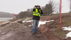 Worker with plastic pipe talking on cell  phone near the trench Stock Footage
