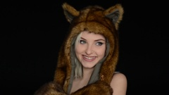 Sexy woman posing in front of the camera in a fur hat on a black background Stock Footage