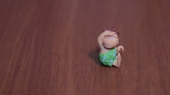 Toy caveman sitting on a dark background cartoon mini Stock Footage