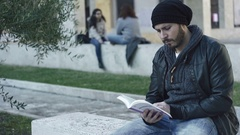 Student sitting on a marble bench studies the book Stock Footage
