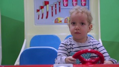 The little boy turns red steering wheel toy fire truck Stock Footage