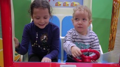 Two kids in a toy fire truck, red steering wheel Stock Footage