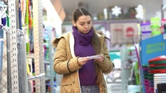 A young woman in a supermarket with a list in the department of household goods Stock Footage