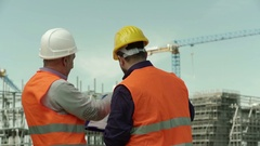 Two engineers at the construction site control work in progress Stock Footage