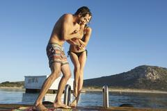 Young couple in bikini and swim trunks playing on sunny summer ocean dock Stock Photos