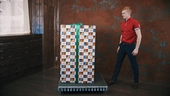 Magician in red polo shirt in studio show focus makes big present box moving Stock Footage