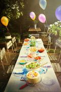Balloons and food at garden party patio table Stock Photos