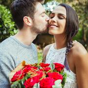 Affectionate man giving red rose bouquet to girlfriend, kissing her on cheek Stock Photos