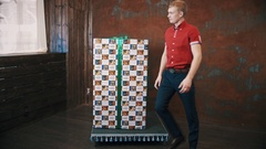 Magician in red polo shirt in studio show trick makes big present box moving Stock Footage