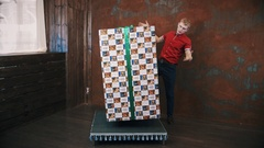 Magician in red polo shirt in studio show trick makes big present box levitate Stock Footage