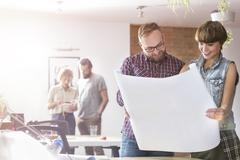 Design professionals reviewing blueprints in office Stock Photos