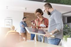 Smiling design professionals reviewing storyboard in office Stock Photos