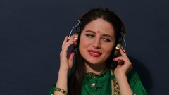 Young happy Indian woman listening to music on headphones Stock Footage