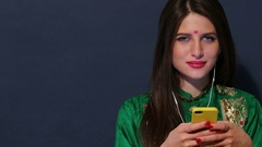 Young Indian girl in green sari listening to the music on headphones Stock Footage