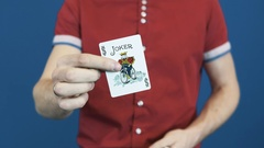 Close up magician in red shirt shuffle playing cards, show Jocker to camera Stock Footage