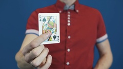 Close up illusionist in red shirt shuffle playing cards, show Queen of Spades Stock Footage